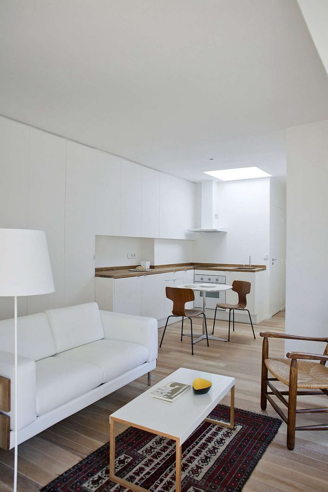 Above the 32 square meter 344 square foot apartment opens to a living space with an ikea kitchen tucked into the corner in place of beige pile carpeting