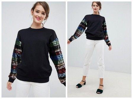 Para tus outfits más urbanos apuesta por una sudadera de color negro con  mangas de lentejuelas arcoíris. Lleva cuello redondo cab19bfce06